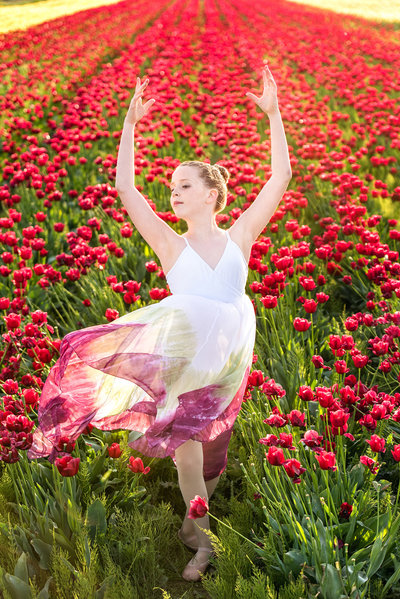 tween girl dressed in white dance dress dancing in red tulip field near Vancouver Washington by Kim Blau Photography