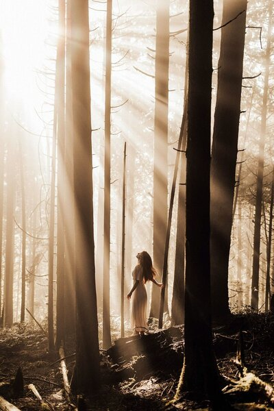 woman standing in forest with sun shining through trees