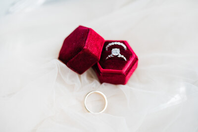 Red mrs ring box with engagement and wedding bands on tulle veil. NJ winter wedding at The Ryland Inn