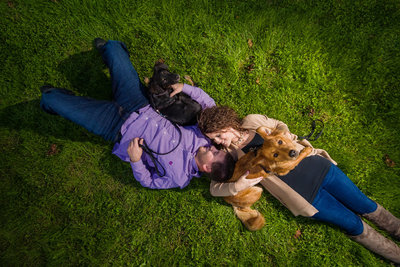 Engaged couple with dogs in grass