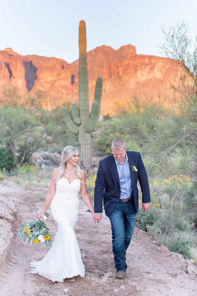 Bride and groom walk hand in hand away from the Superstition mountains