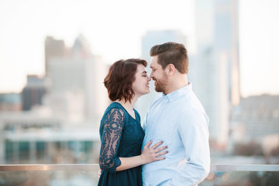 Engaged couple smiles nose to nose on a rooftop in downtown Tampa