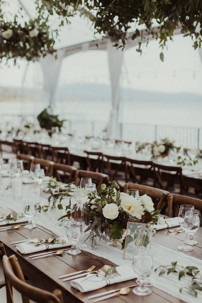 wedding reception tables with glasses and white flowers
