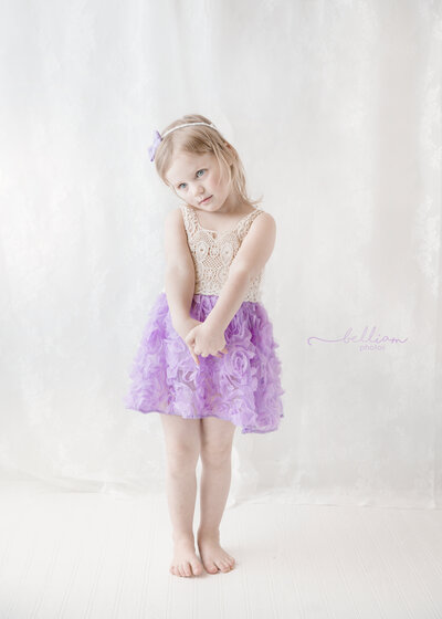 3 year od girl in a white and purple dress on a white background