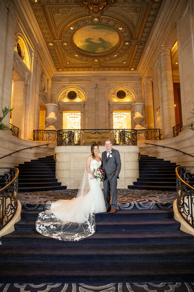 A classic wedding photo at gorgeous stairs and architecture at the Hilton Towers in Chicago, IL