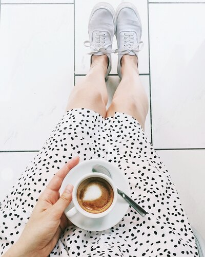 Woman holding coffee in white polka dot dress