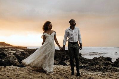 bride and groom walking next to ocean