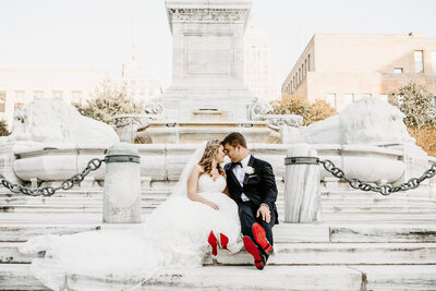 Bride and groom sat in front of monument with red sole shoes
