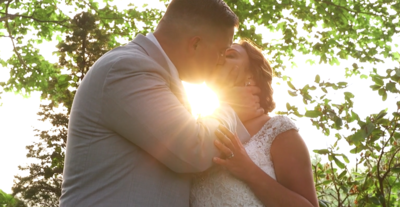 Scene from Cape Cod wedding film of couple kissing sun behind the trees