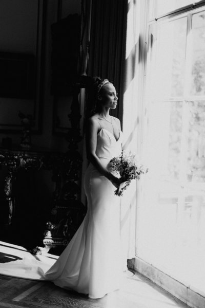 bride stands in front of window at the larz anderson house in washington dc holding her bouquet the image is in black and white