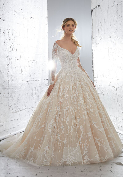 Stunning Tulle Ballgown Accented in Delicate Beaded Embroidery. The Plunging, Off-the-Shoulder Neckline and Delicately Beaded Illusion Sleeves add a Touch of Romance. Covered Button Details Along the Back and a Wide Horsehair Hemline Complete the Look. Available in Three Lengths: 55″, 58″, 61″. Shown in Ivory/Nude