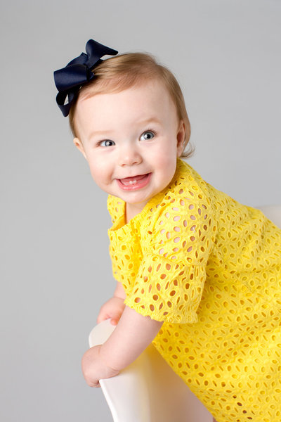 baby girl in yellow smiles against a grey background