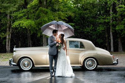 Bride and groom smile in front of an old car in the rain on their wedding day
