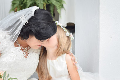 Bride and flower girl giggling on the front porch of their all inclusive wedding venue