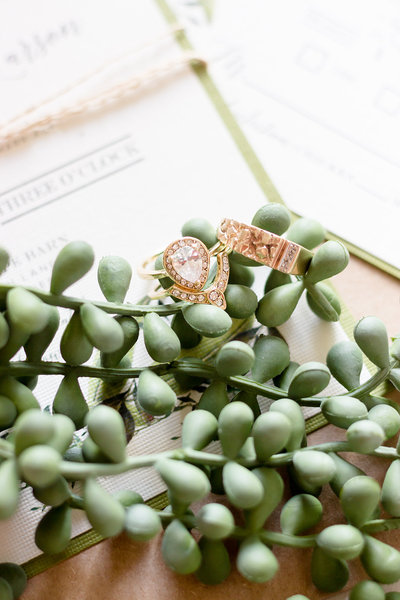 Gold Pear Shaped Wedding Ring with matching band laid on wedding invitations and wedding flowers at the Scenic Escape Barn in Henderson Minnesota