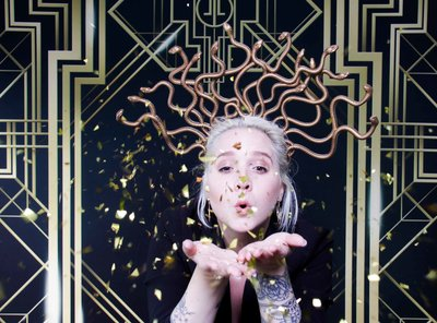 lady blowing confetti front of a gatsby backdrop