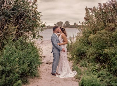 Wedding Couple kissing on the beach with the bride wearing a flower crown