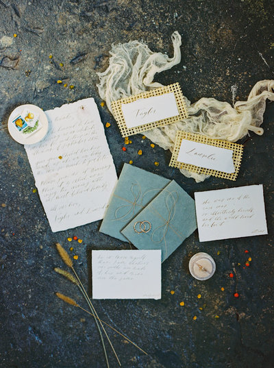 Cane weave place cards, dusty blue vow books and hand-calligraphed wedding vows in a styled flatlay