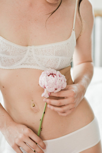 Woman in white lingerie holding pink peony