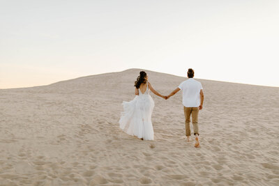 newlyweds holding hands running through sand dune