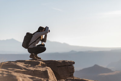 woman taking a picture while on a cliff