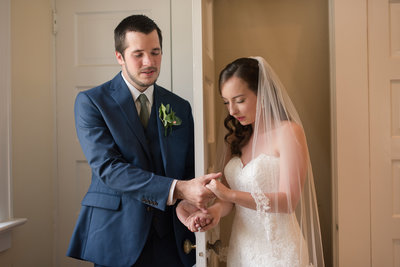 bride and groom hold hands in prayer at womans club of portsmouth in virginia