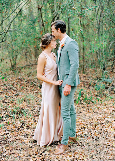 Tender forehead kiss between bride and groom for an intimate fall wedding in a South Carolina forest