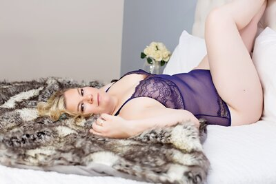 blonde woman in purple lingerie laying on her back on a faux fur rug posing for a boudoir portrait at boudoir by Janet Lynn Photography