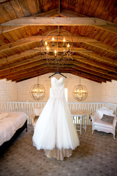 Wedding gown hangs from the bridal suite chandelier at Wildberry Farm