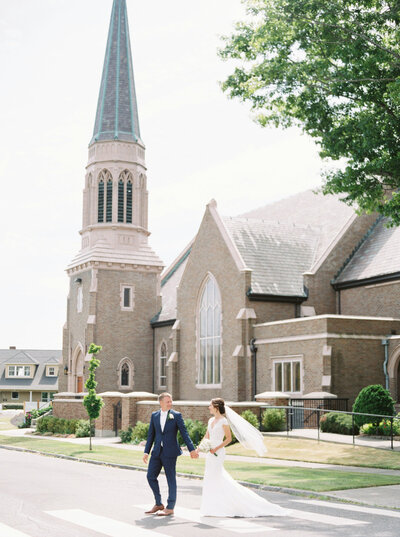 bride and groom walking across the street with the church behind them in Bellingham Washington