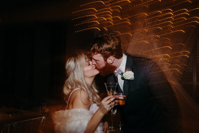 bride and groom kissing holding drinks