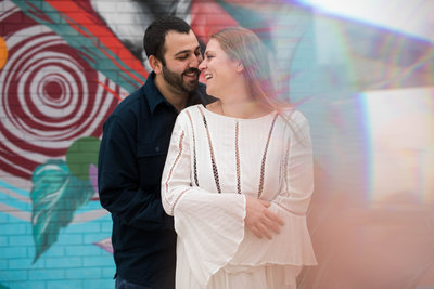 Engagement photo of couple smiling with colorful background