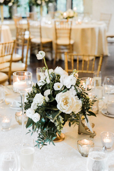 White and green centrepiece by Blush and Bloom with gold chairs