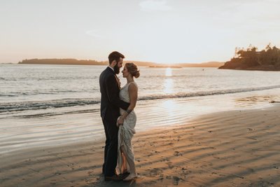 bride and groom on the beach dancing in the sunset light