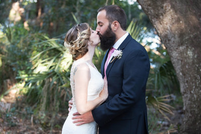 Bride and groom kissing in wooded area of Philippe Park Safety Harbor FL