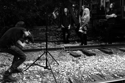 Behind the scenes Nashville Tennesse photoshoot Mark Maryanovich photographing Juliana Hale And Band of Roses standing against trailer and trees black and white image