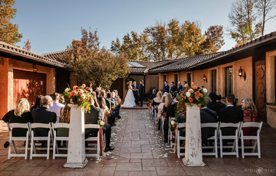 An outdoor wedding ceremony in the courtyard at Villa Parker in Colorado during Autumn