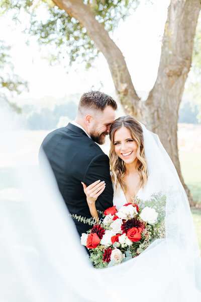 Joyful Portrait of the Bride and Groom with Veil