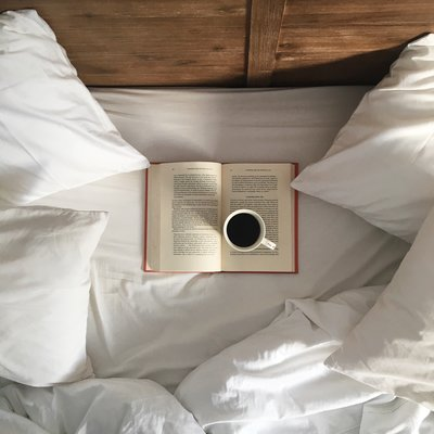 flatlay of cup of coffee and a book on an unmade bed