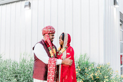 bride and groom in their Hindu wedding attire smiling at each other
