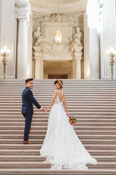 vietnamese emerican couple standing on grand staircase at city hall on wedding day