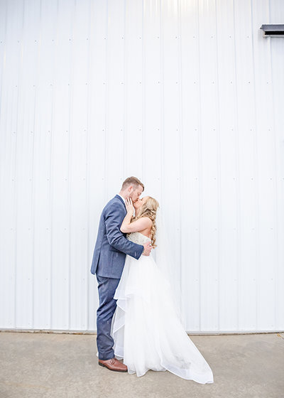 Bride and groom kiss by white barn on wedding day