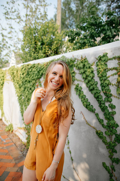 woman standing in front of wall wearing yellow jump suit and smiling