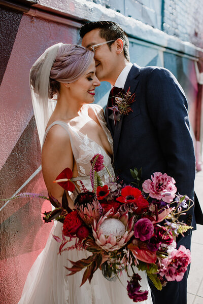 Fun and colorful bride and groom kiss on their wedding day with large bohemian bouquet