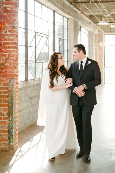 Bride and groom walking down hallways smiling