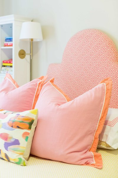 A pink and orange patterned headboard and pillows.