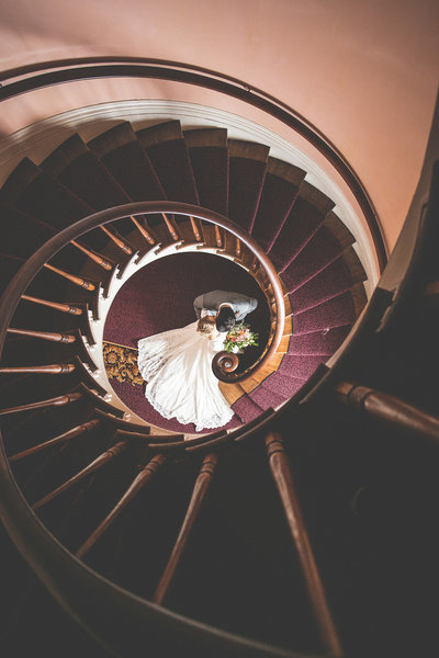 Bride and Groom kissing at the bottom of spiral staircase after wedding in Madison, Indiana