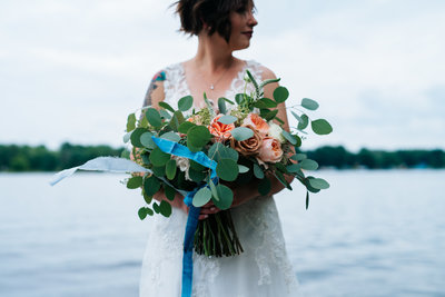 Bride holding bouquet of flowers on edge of the water.