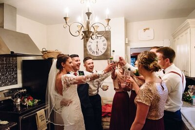 Wedding party toasting in rustic cottage