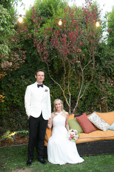 Bride sits on a brightly colored setee while groom holds her hand and stands proudly